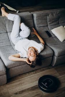 Молодая женщина, лежа на тренере, пока робот пылесос чистит пол