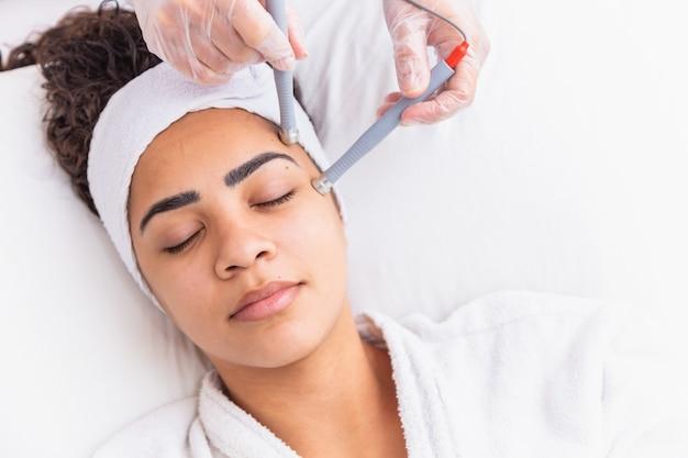 若返りの手順中に美容師のテーブルに横たわっている若い女性。美容師は首と顔の肌の若々しさと健康に気を配ります。ハードウェア面のクリーニング手順。