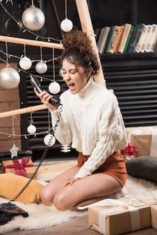 電話で叫んでふわふわのカーペットの上に横たわっている若い女性