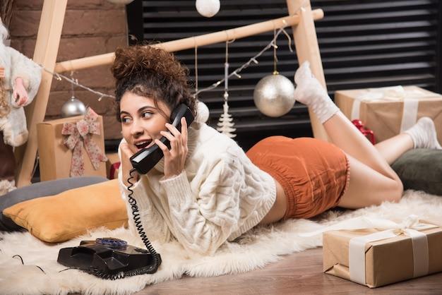 푹신한 카펫에 누워 전화 통화를 하는 젊은 여성