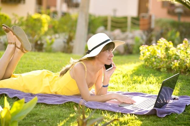 Молодая женщина, лежа на зеленой лужайке, работает на портативном компьютере, подключенном к беспроводному интернету, разговаривает по мобильному телефону в летнем парке. ведение бизнеса во время карантина.