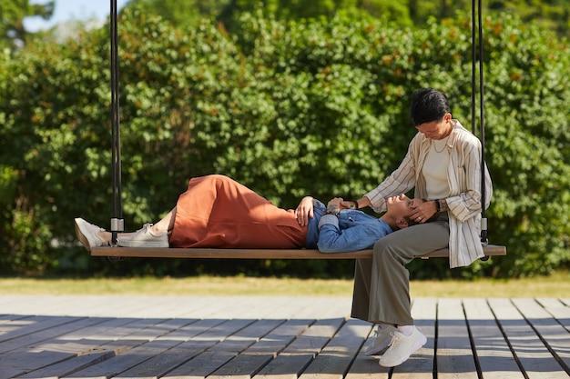彼らが屋外でブランコに時間を費やしている間、彼女のガールフレンドの膝の上に横たわっている若い女性