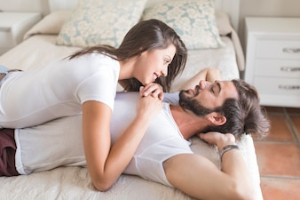 Young woman lying on man on bed