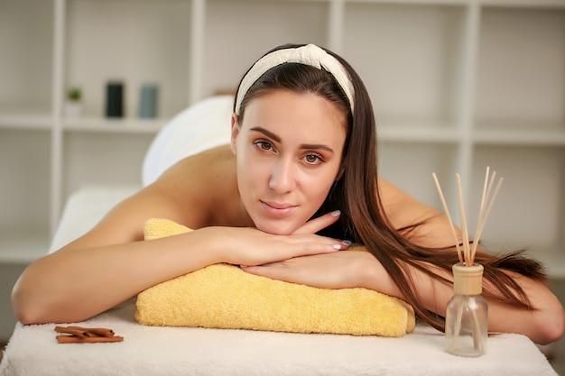 Молодая женщина, лежа на массажной кровати в спа и оздоровительном центре.