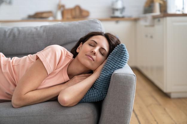 Молодая женщина, лежа на подушке на диване, отдыхает, расслабляется, спит после завершения работы по дому