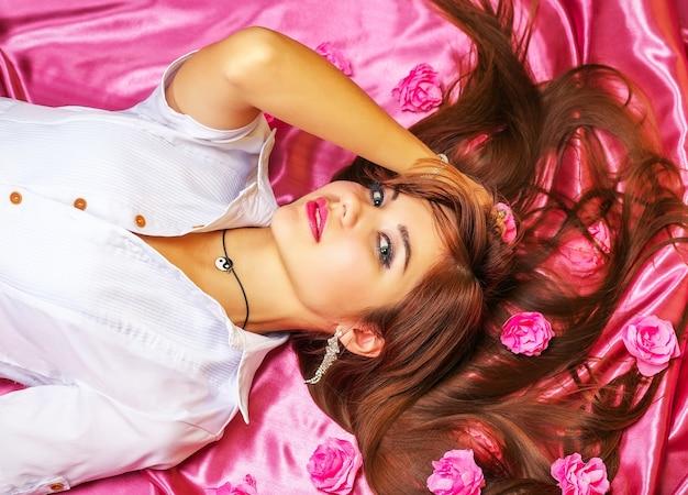 꽃 분홍색 배경에 거짓말을하는 젊은 여자. 긴 머리와 꽃을 가진 아름 다운 소녀
