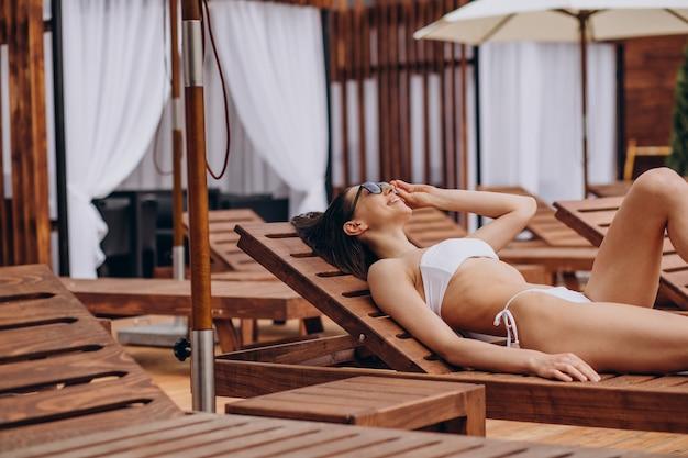 Молодая женщина, лежа на шезлонге у бассейна