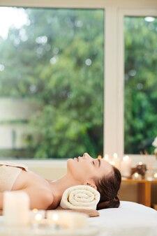 스파 살롱에서 눈을 감고 침대에 누워 있는 젊은 여성