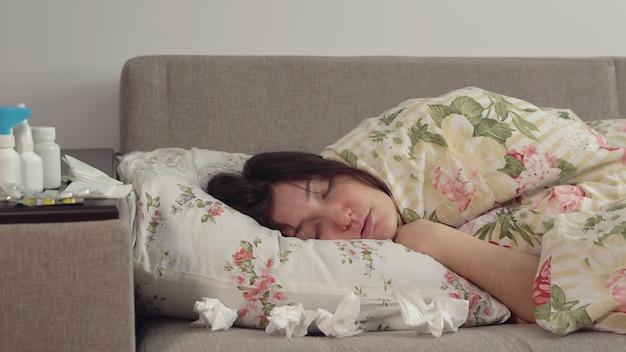毛布に包まれたベッドに横たわっている若い女性。