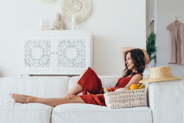 Молодая женщина, лежа на диване с фруктами.