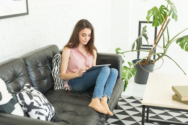タブレットで暗いソファに横たわって若い女性