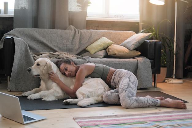 Молодая женщина лежит на полу в комнате вместе со своей собакой и смотрит фильм онлайн на ноутбуке