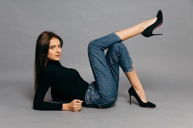 Молодая женщина, лежа на полу, изолированные на сером фоне. фото высокого качества