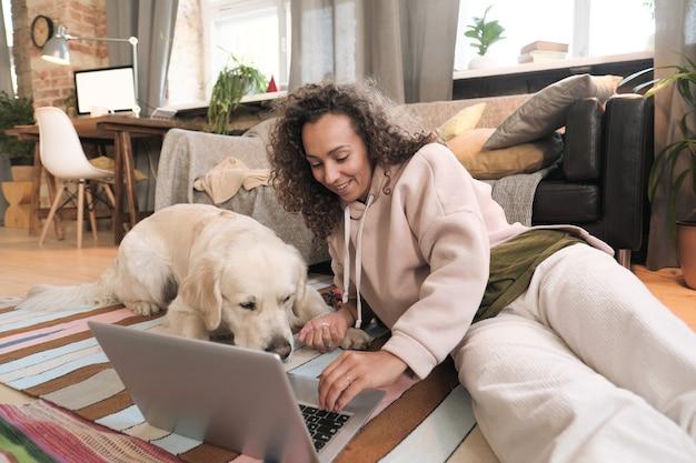 Молодая женщина, лежа на полу со своей собакой и используя портативный компьютер в гостиной