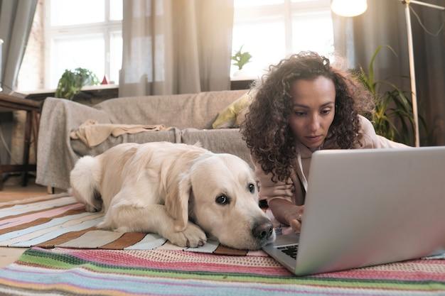 彼女の犬と一緒に床に横たわって、自宅の部屋でラップトップでオンラインで作業している若い女性