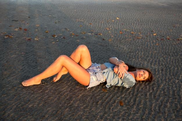 日没時に砂の上に横たわって若い女性