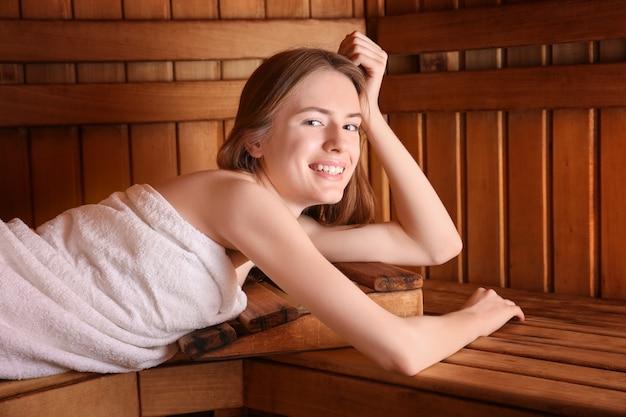 사우나에서 나무 벤치에 누워 젊은 여자