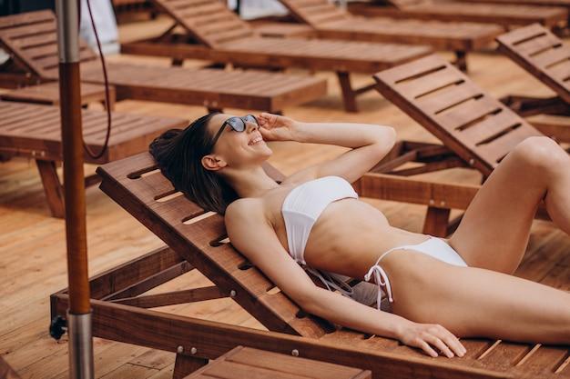 Giovane donna sdraiata sul lettino a bordo piscina