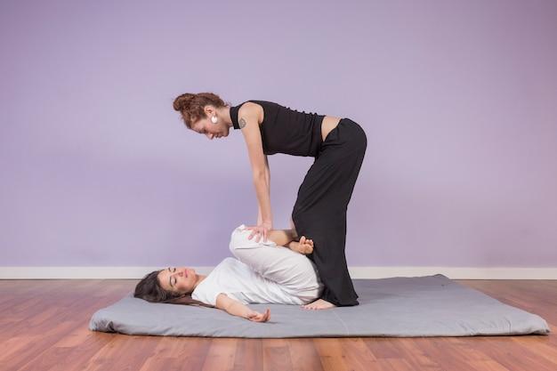Молодая женщина лежит, наслаждаясь растяжками и точечным массажем традиционного тайского массажа в оздоровительном спа-центре