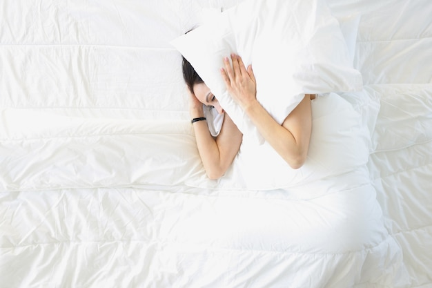 Young woman lying in white bed and covering her ears with pillow top view until when can you