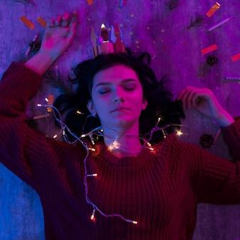 Молодая женщина, лежа с рождеством светящиеся огни празднования.