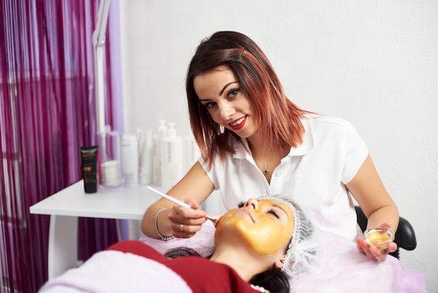 Young woman lying with closed eyes and cosmetologist applying gold facial mask by brush in spa