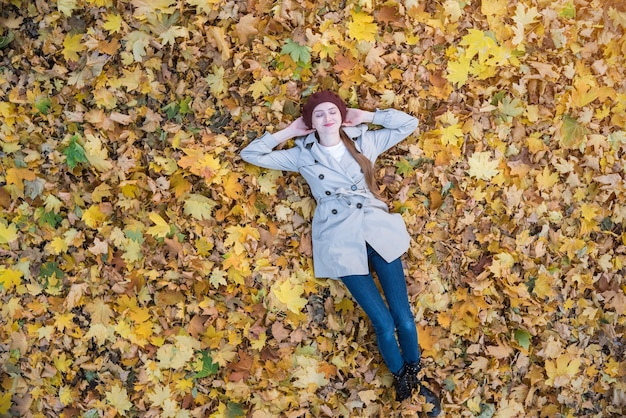 Young woman lying on yellow leaves in forest