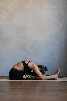 Young woman lying on a yoga mat. girl bent down to her feet, practice stretch exercise at yoga class.