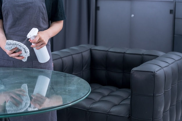 Молодая горничная в фартуке убирает, протирает поверхность офисного стеклянного стола средством для чистки бутылочек, влажной тряпкой, крупным планом, образом жизни, реальными людьми.