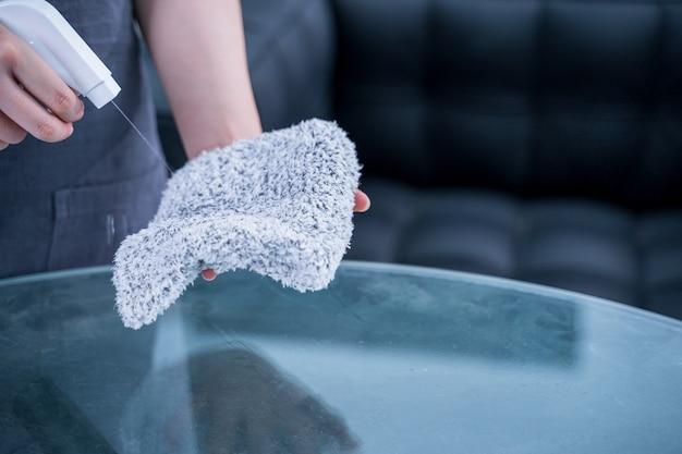 エプロンの若い女性のメイドは、スプレーボトルクリーナー、ウェットラグ、クローズアップ、ライフスタイル、実在の人々でオフィスのガラステーブルの表面を掃除し、拭いています。