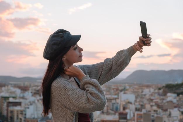 若い女性は屋外で彼女の携帯電話で自画像を作成します