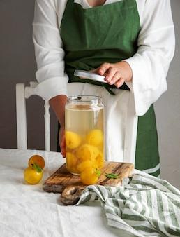 Молодая женщина делает компот из желтых слив. консервация в стеклянной банке. заготовки на зиму, впрок