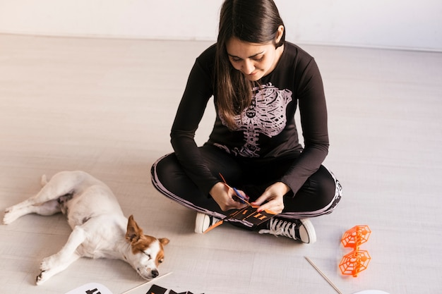Young woman makes halloween garland.creative diy . home decor project party.halloween crafts inspiration. cuet small dog besides