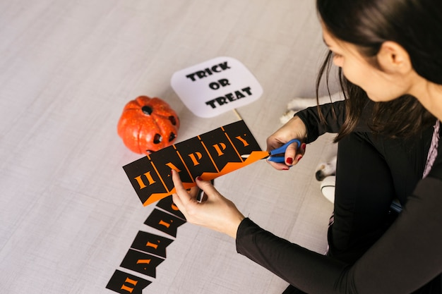 Young woman makes halloween garland.creative diy . home decor project party.halloween crafts inspiration.