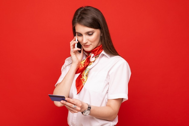 A young woman makes an order online by mobile phone and bank card
