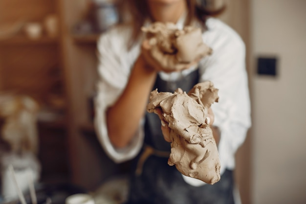 Young woman makes pottery in workshop
