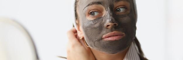 若い女性が若返りの粘土のフェイスマスクを作ります