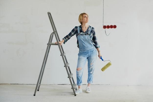Молодая женщина делает ремонт в своем доме