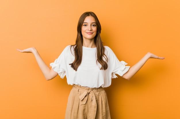 Молодая женщина делает весы руками, чувствует себя счастливой и уверенной