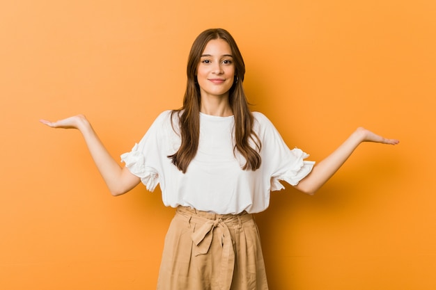 Young woman makes scale with arms, feels happy and confident
