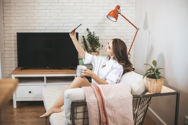 Young woman makes selfie sitting on couch at home. young person drinks coffe in big mug and use smartphone
