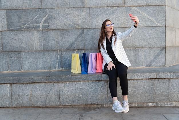 若い女性は、カラフルなバッグで自分撮りをします。ファッションブロガー。お買い物後。