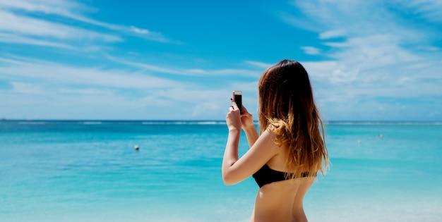 젊은 여자는 그녀의 전화를 가진 landcape 사진 만들기. 아름다운 푸른 바다와 하늘을 촬영.