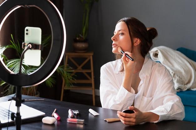 Молодая женщина делает видеоблог макияжа со своим смартфоном