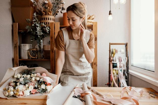 Молодая женщина делает красивую цветочную композицию