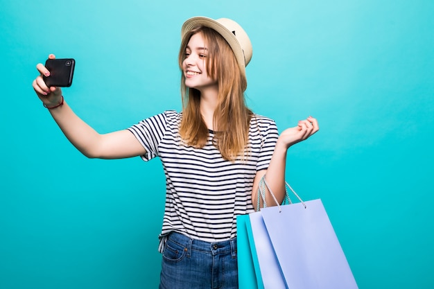 ショッピングのための色のバッグで座っているスマートフォンでselfieを作る若い女性
