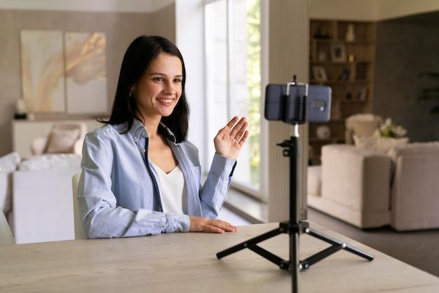 彼女の携帯電話で自宅でvlogを作る若い女性