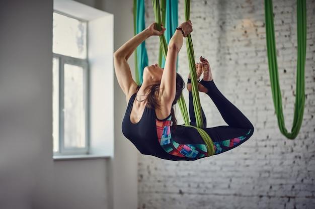 ロフトのインテリアで反重力ヨガの練習を作る若い女性