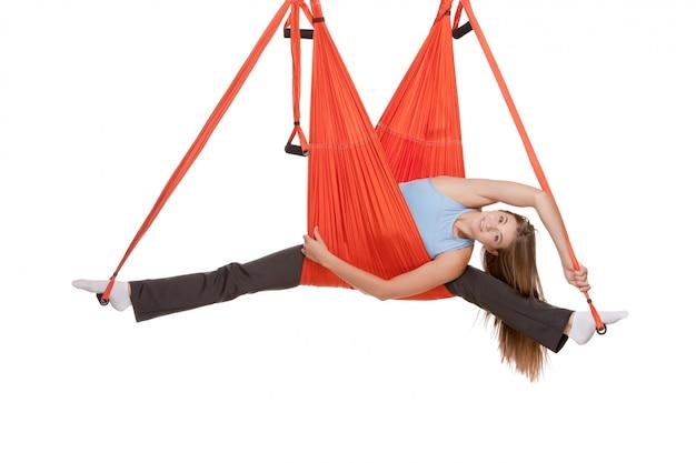 ひものストレッチで反重力ヨガの練習を作る若い女性