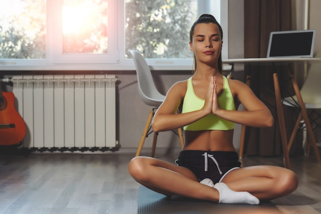 Young woman making breathing exercise on yoga mat at home